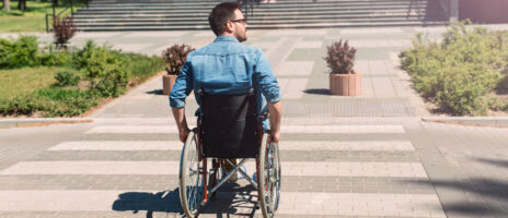 young,handicapped,man,in,wheelchair,crossing,street,carefully